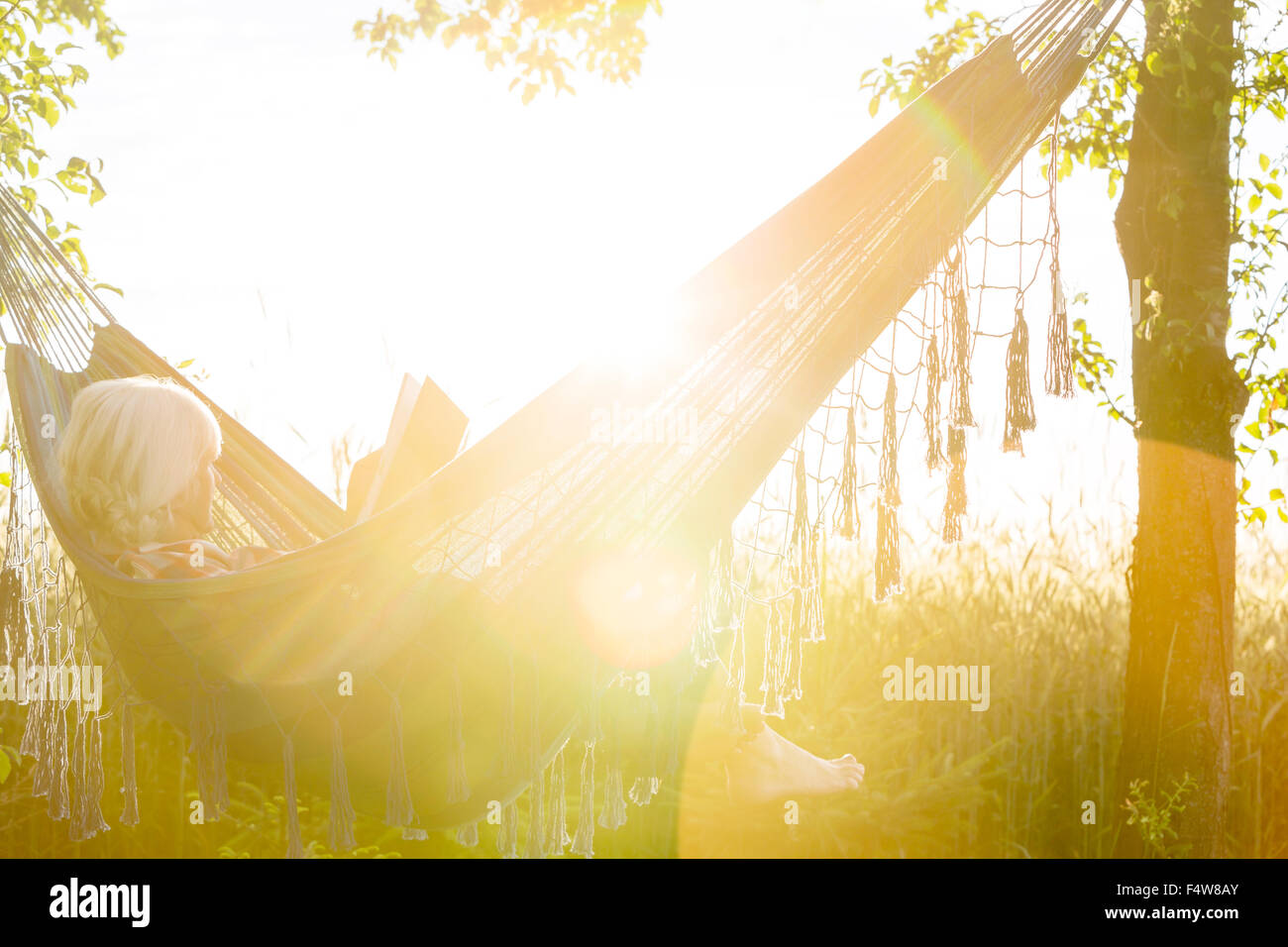Serene woman reading book in sunny hammock - Stock Image