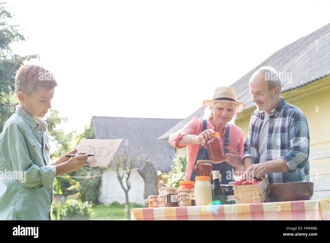 Grandparents and grandson preparing to sell honey - Stock Image