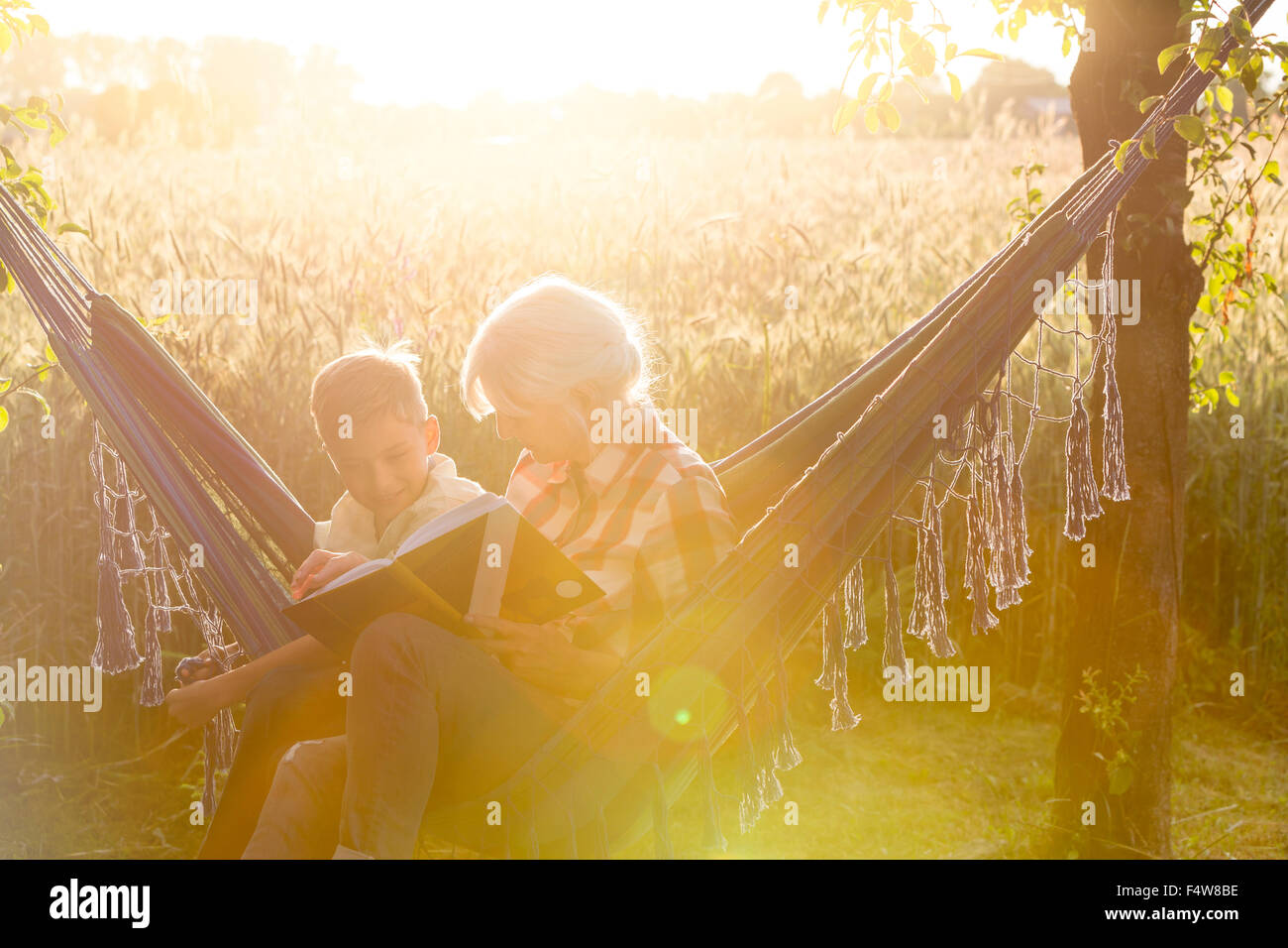 Grandmother and grandson reading book in sunny rural hammock - Stock Image