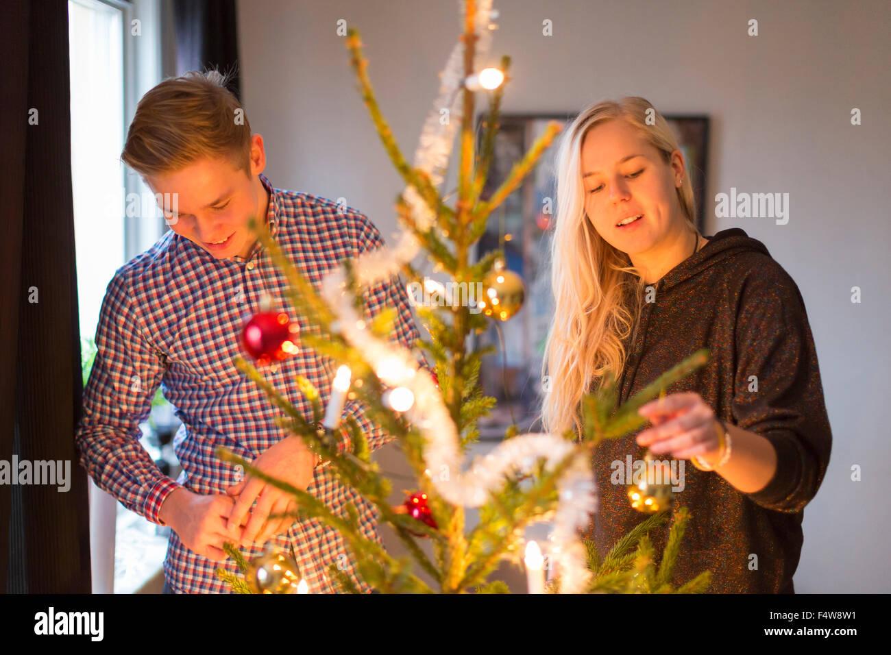 Couple decorating Christmas tree - Stock Image