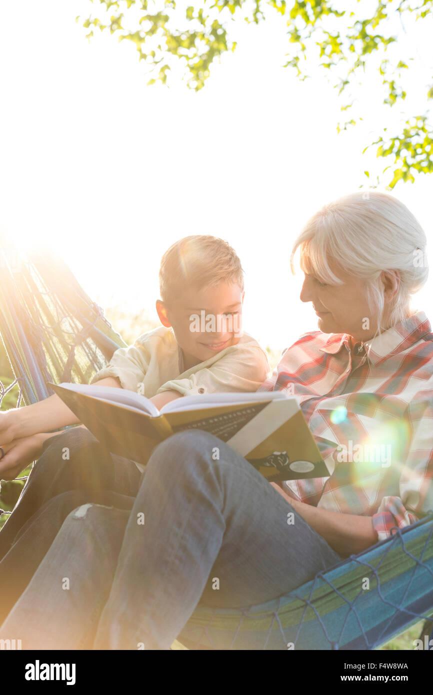 Grandmother reading to grandson in sunny hammock - Stock Image