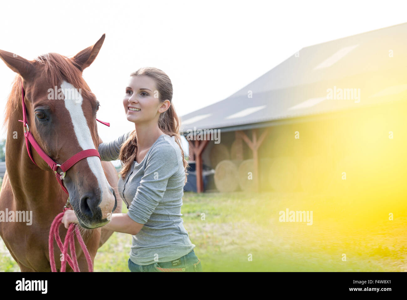 Smiling woman with horse outside rural barn - Stock Image