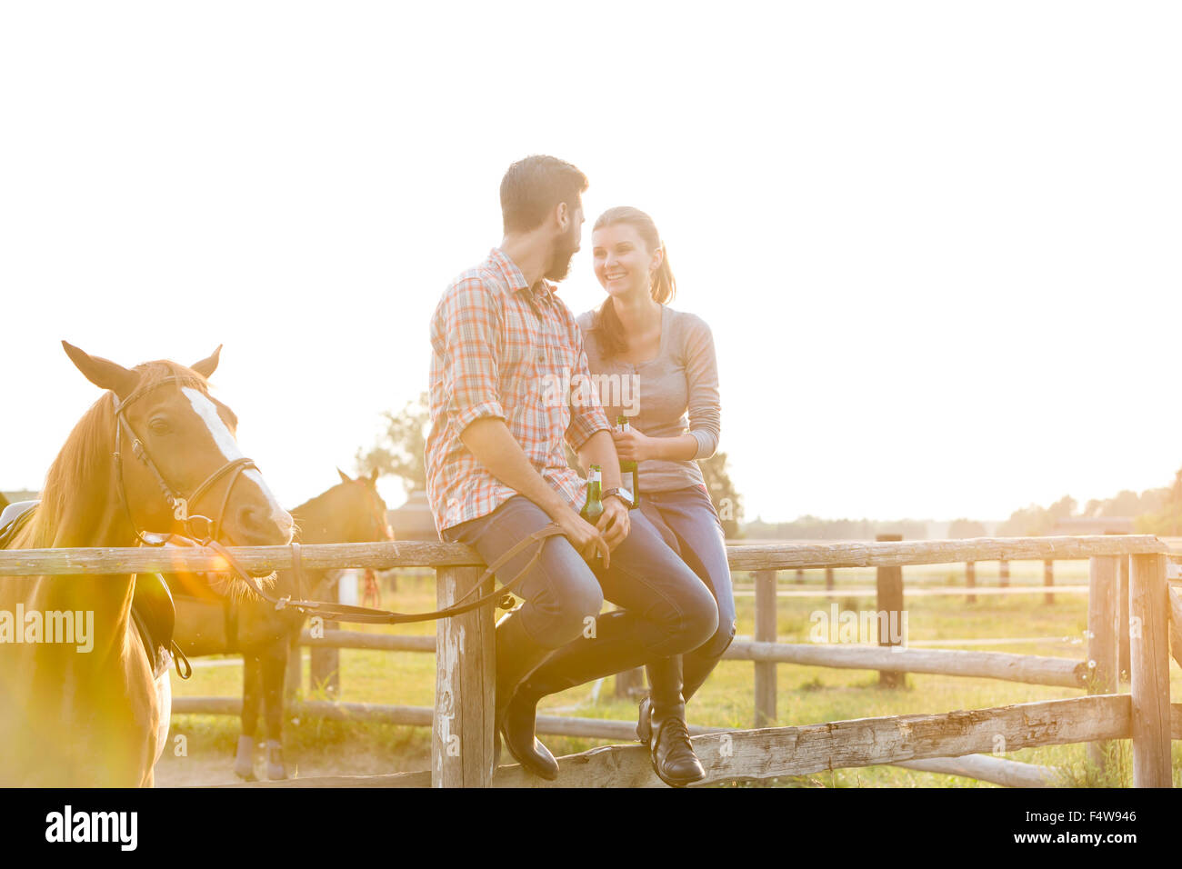 Couple with horse talking on sunny rural pasture fence Stock Photo