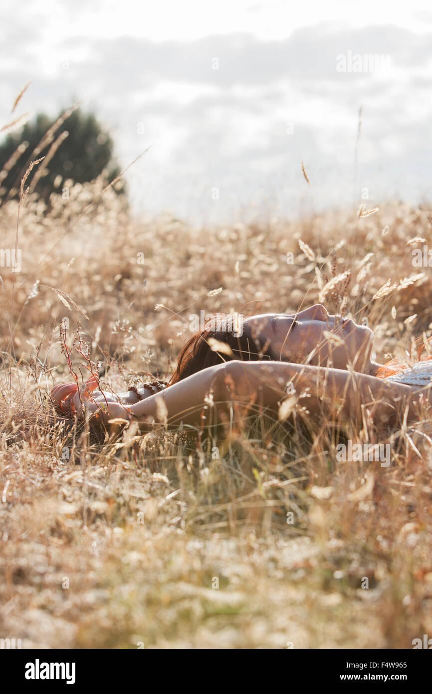 Serene woman sleeping in sunny rural field - Stock Image