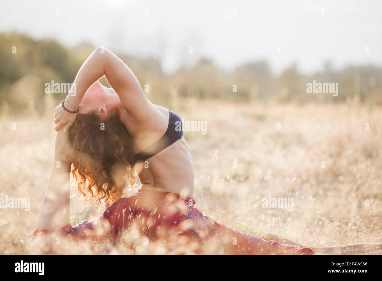 Woman in royal king pigeon yoga pose in rural field - Stock Image