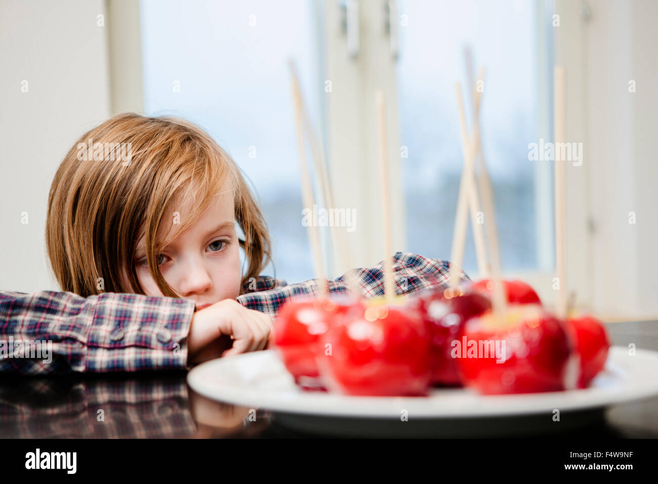 Girl (6-7) looking at taffy apples - Stock Image