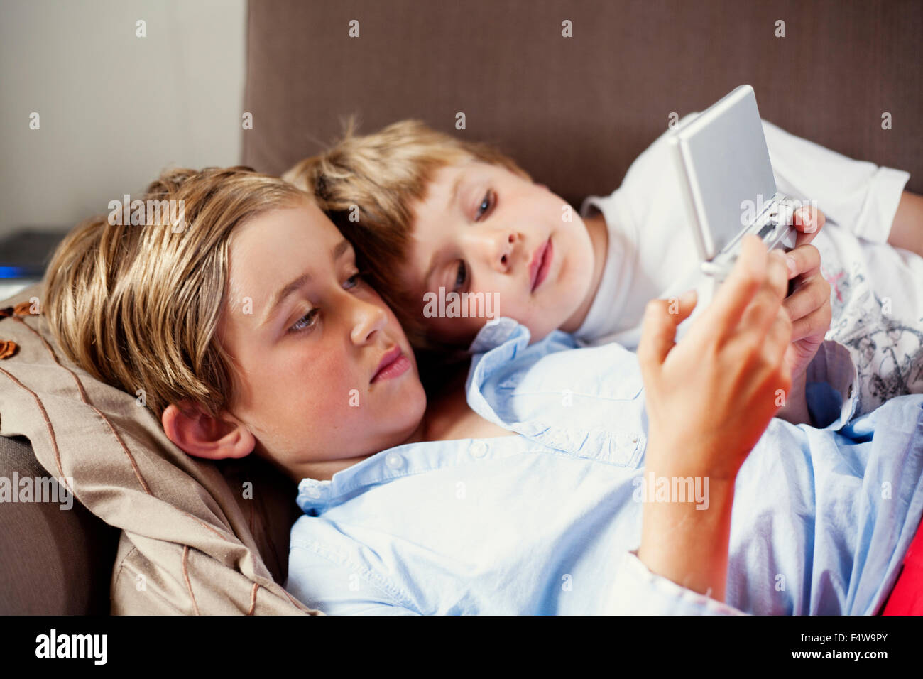 Sweden, Uppland, Runmaro, Barrskar, Brothers (4-5, 6-7) playing on game console - Stock Image