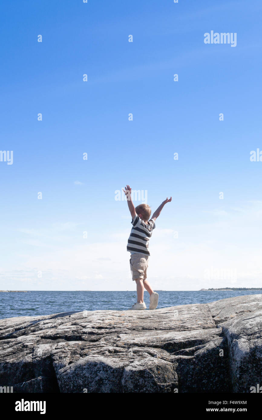 Sweden, Uppland, Runmaro, Barrskar, Boy (6-7) standing on seaside and looking at view - Stock Image