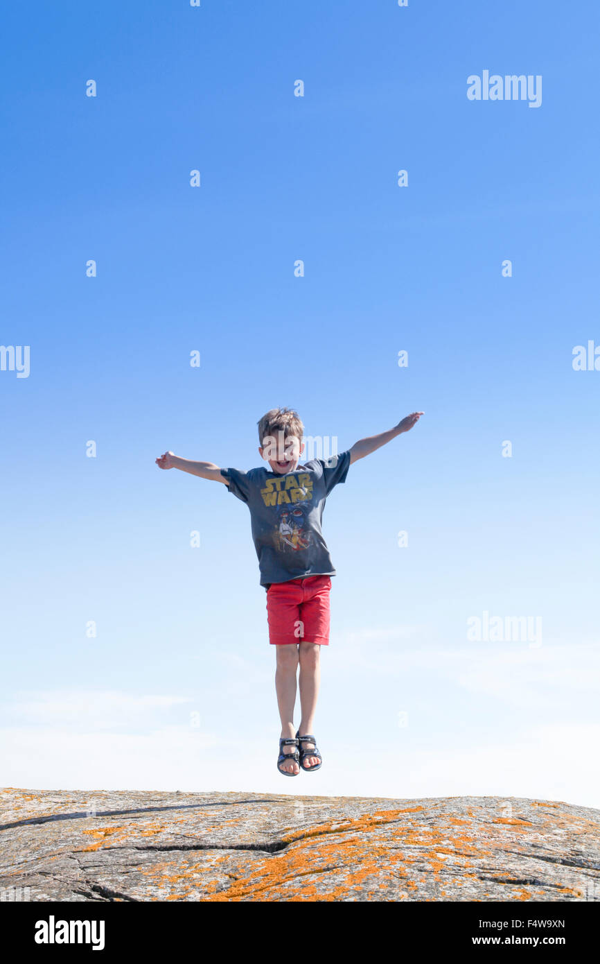 Sweden, Uppland, Runmaro, Barrskar, Boy (6-7) jumping on rock - Stock Image