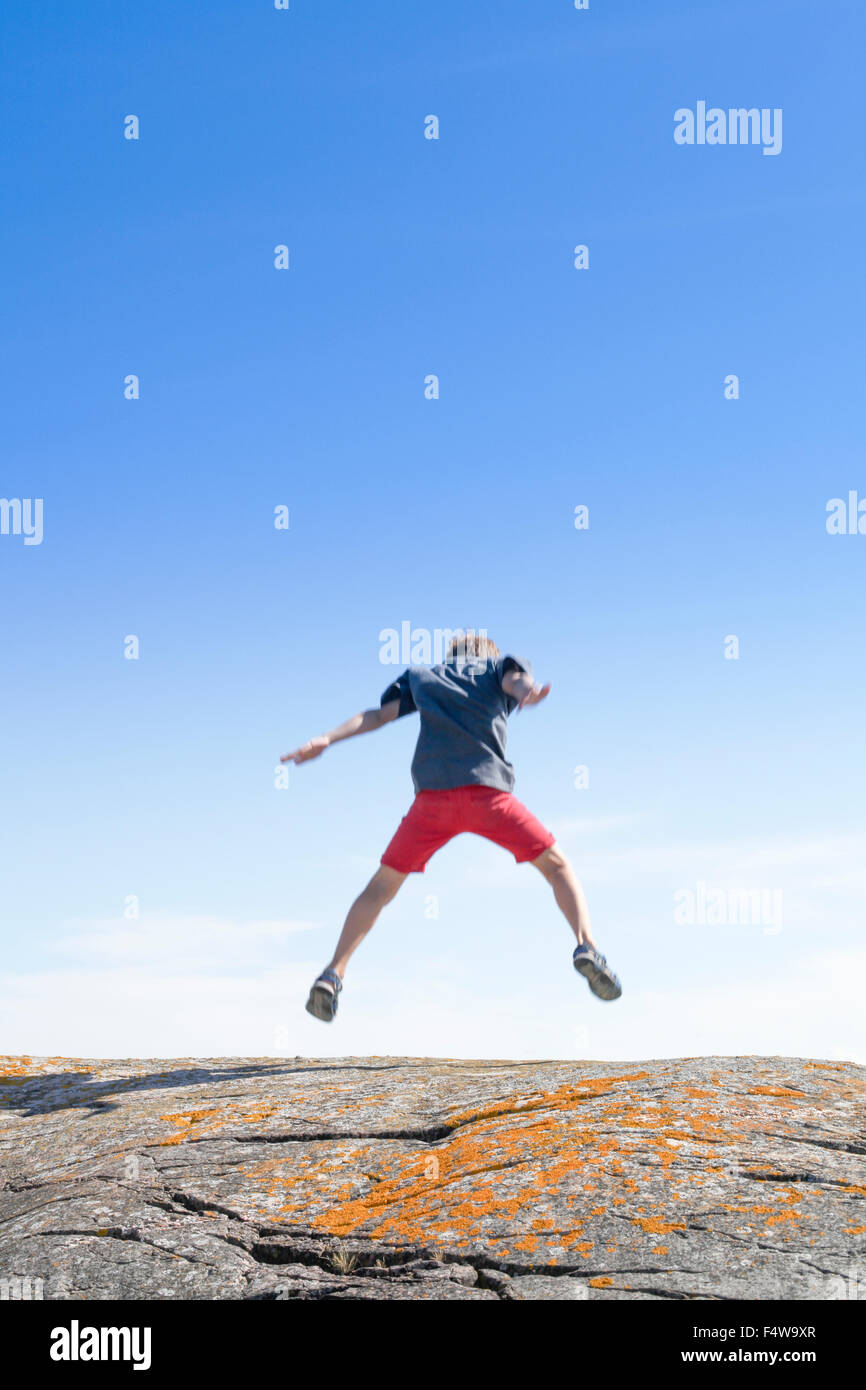 Sweden, Uppland, Runmaro, Barrskar, Boy (6-7) jumping on rock, Rear view - Stock Image