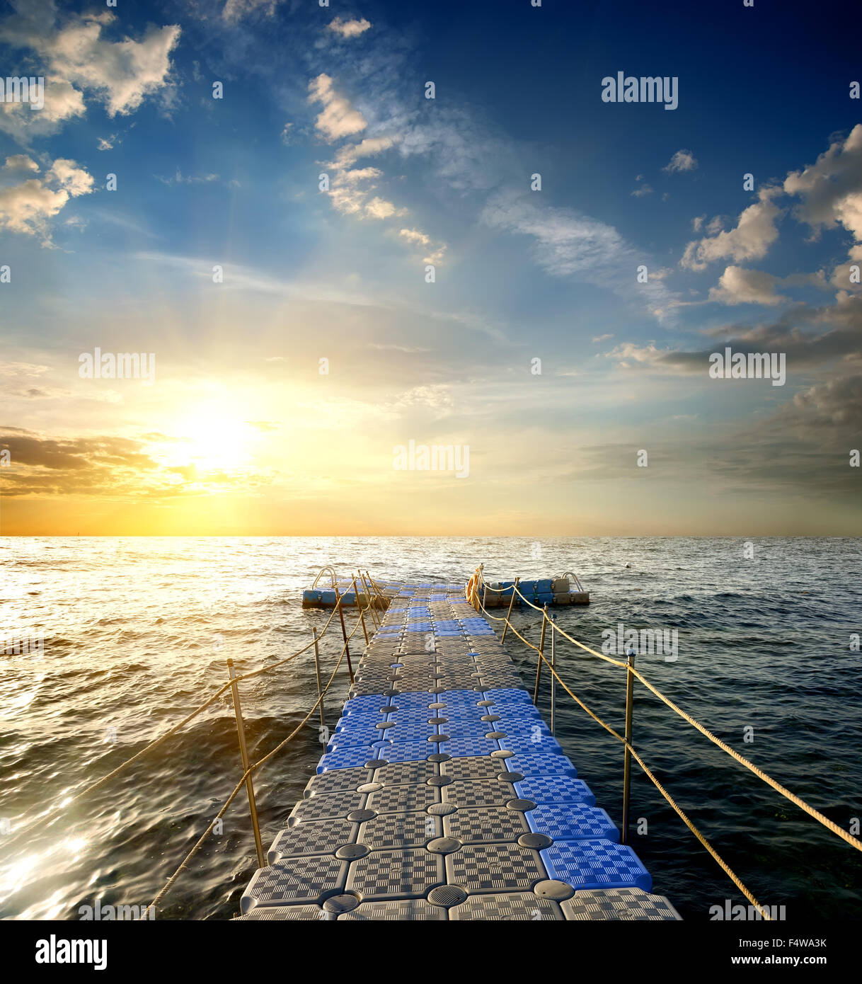 Pontoon with handrails in the sea at sunset - Stock Image