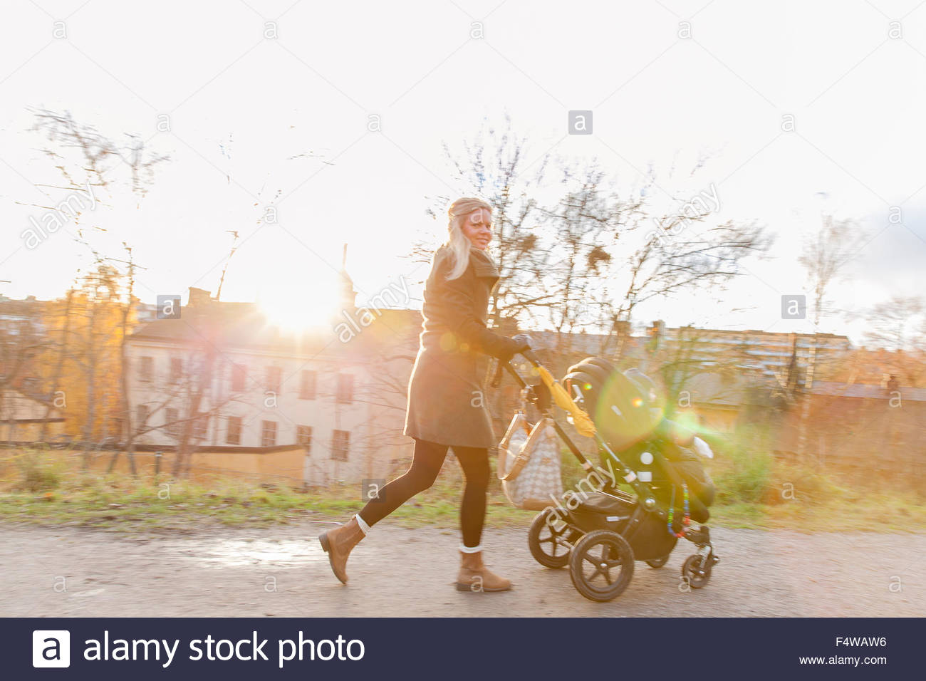 Sweden, Stockholm, Sodermalm, Young mother walking with son (6-11 months) sitting in stroller - Stock Image