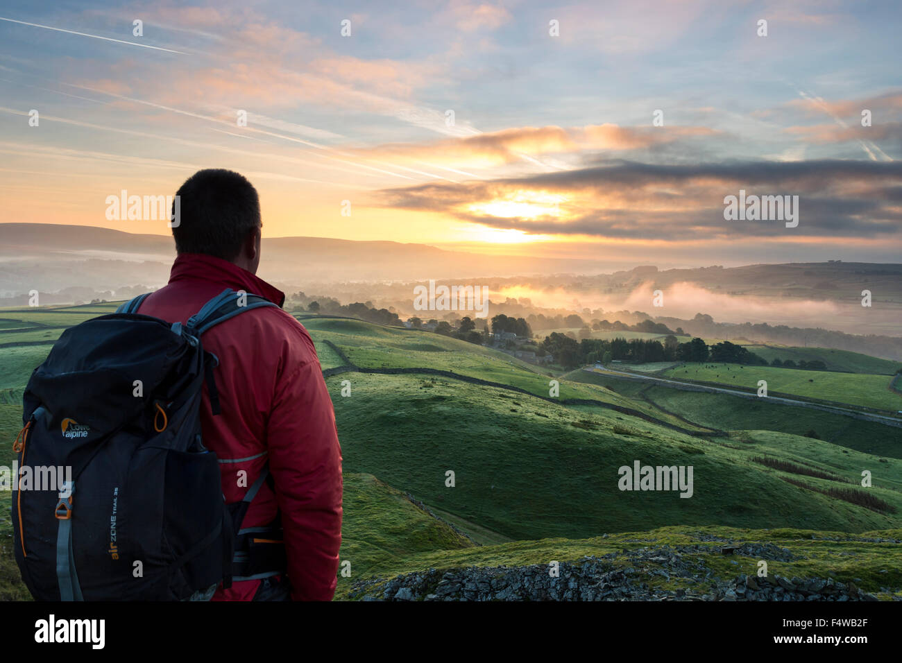 Hiker Enjoying the View Across a Misty Teesdale at Sunrise From Kirkcarrion, Lunedale, Teesdale County Durham UK - Stock Image