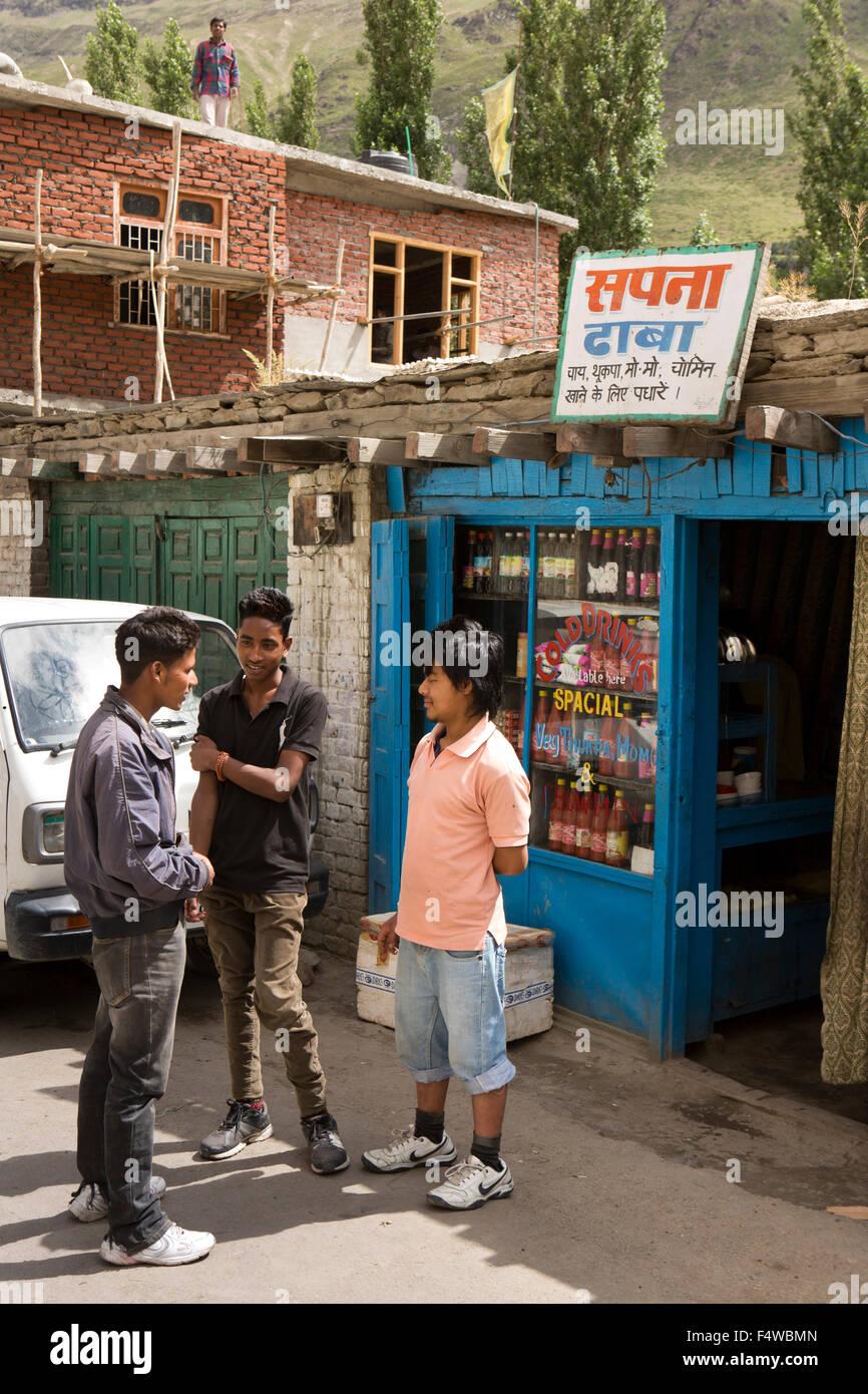 India, Himachal Pradesh, Lahaul and Spiti, Keylong Bazaar, young men talking outside small cafe - Stock Image