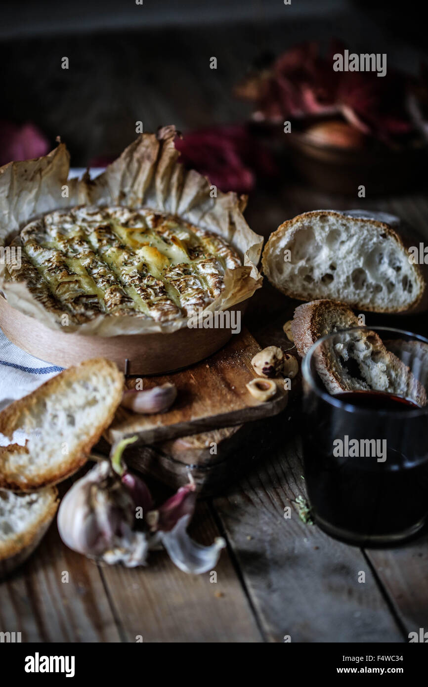 Baked Coulommiers cheese and garlic bread on a wooden, rustic table. - Stock Image