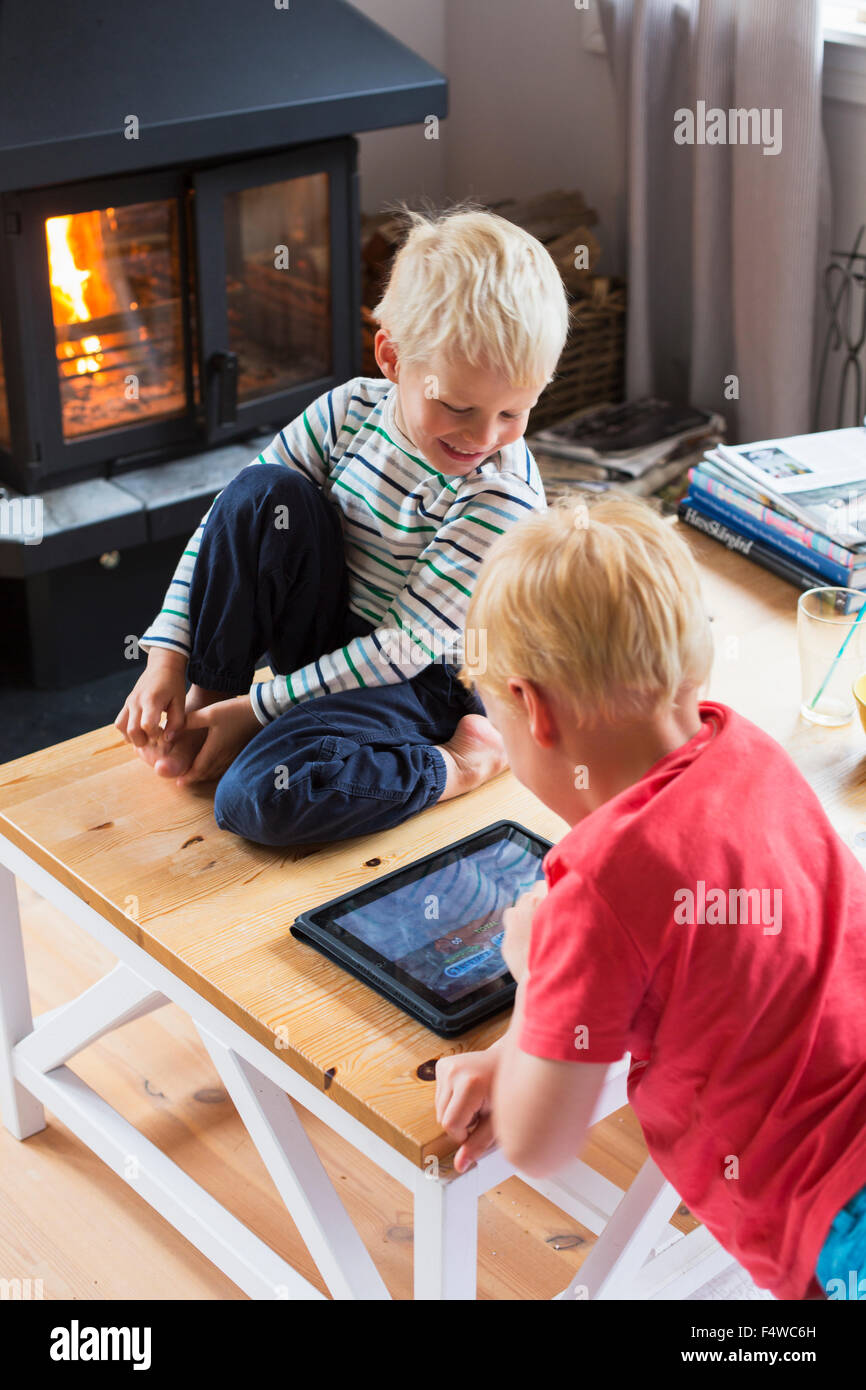 Boys (4-5, 6-7) playing with digital tablet at home - Stock Image