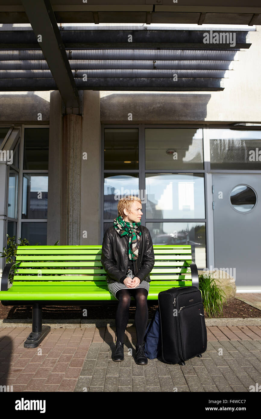 Sweden, Harryda, Landvetter, Woman sitting on bench at the airport - Stock Image