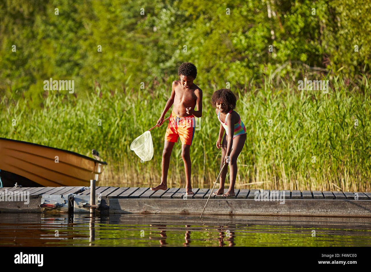 Sweden, Vastra Gotaland, Skagern, Girl (6-7) and boy (10-11) fishing in lake - Stock Image