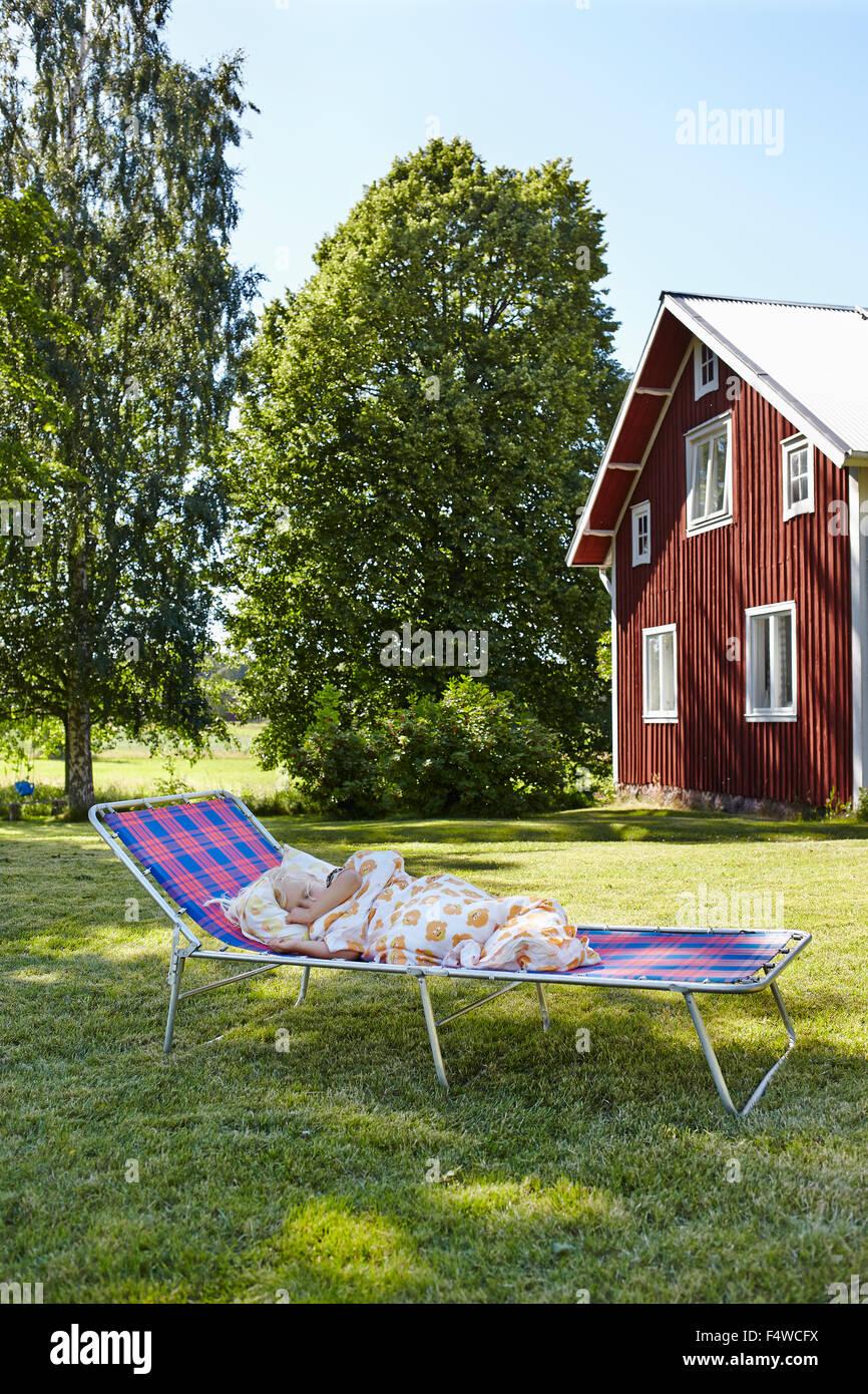 Girl (4-5) sleeping on sun lounger in front yard - Stock Image