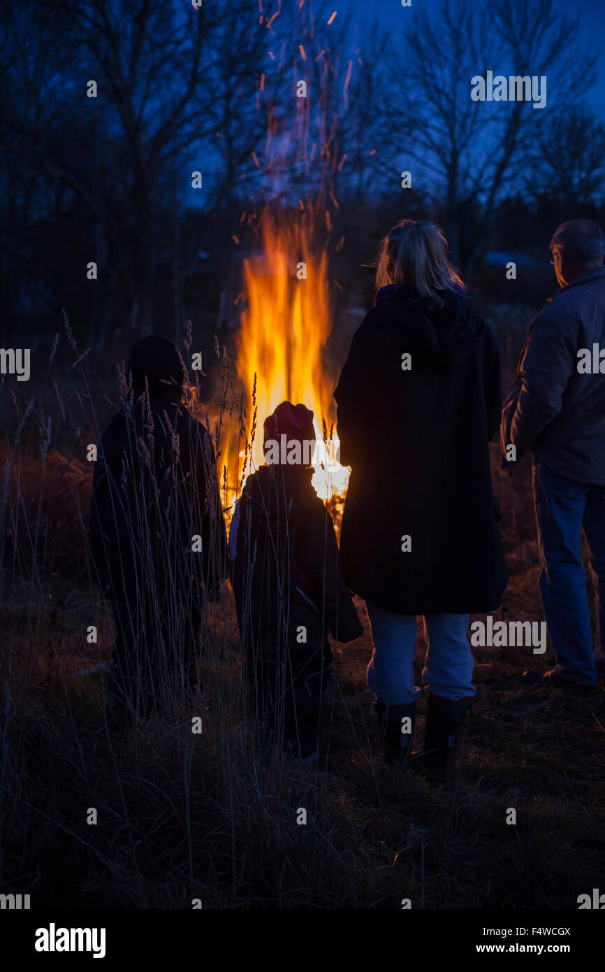 Sweden, Narke, Filipshyttan, Grandfather with grandchildren (6-7,8-9,16-17) looking at bonfire Stock Photo