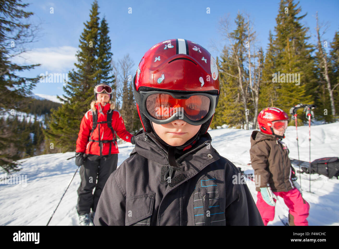 Norway, Osterdalen, Trysil, Mom and her two children (4-5, 8-9) walking down ski slope - Stock Image