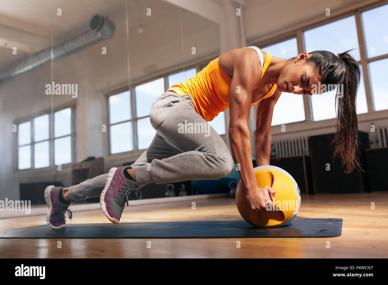 Fit female doing intense core workout in gym. Young muscular woman doing core exercise on fitness mat in health - Stock Image