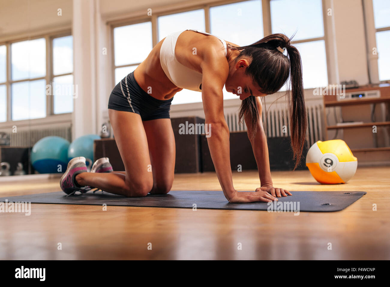 Shot of young woman stretching her back. Muscular woman exercising on fitness mat in gym. - Stock Image