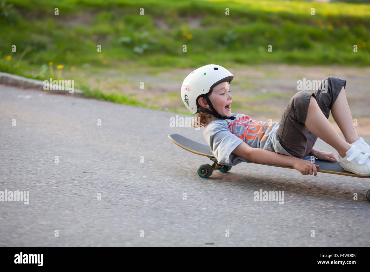 Sweden, Vastergotland, Lerum, Boy (8-9) sliding down street on skateboard - Stock Image