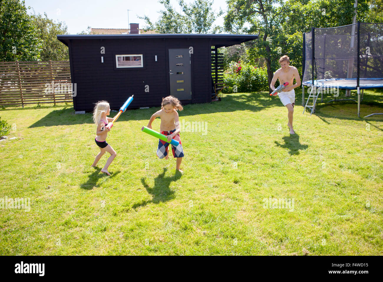 Siblings (8-9, 10-11) playing with water guns in backyard - Stock Image