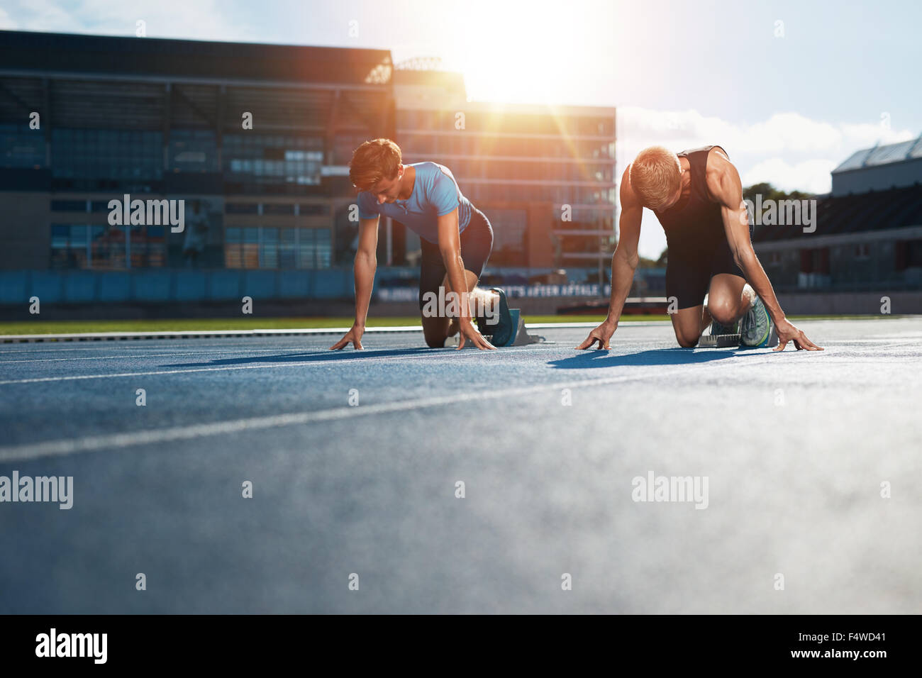 Young athletes preparing to race in start blocks in stadium. Sprinters at starting blocks ready for race with sun - Stock Image