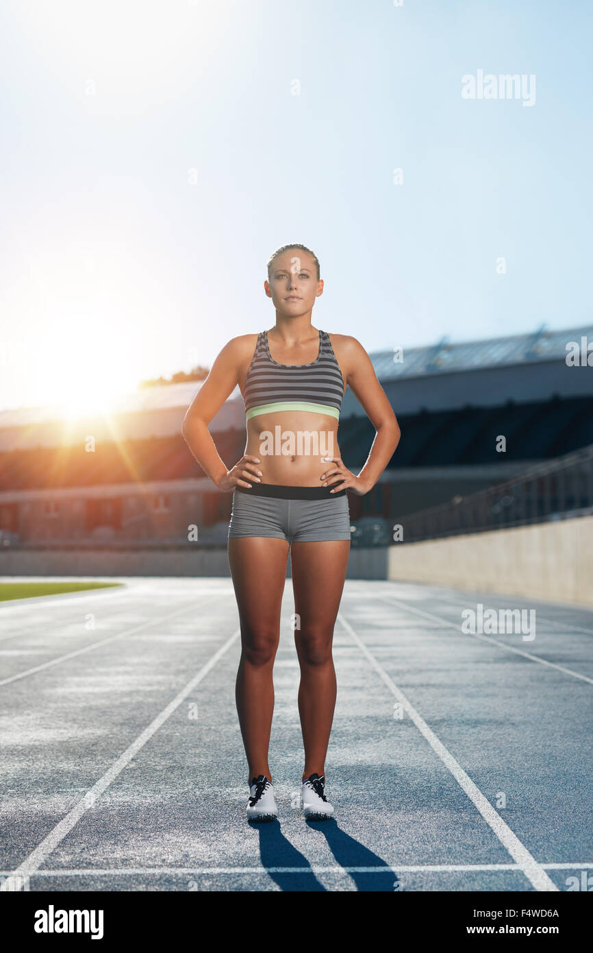 Full length shot of professional female athlete standing with her hands on hips looking confidently at camera. Runner - Stock Image