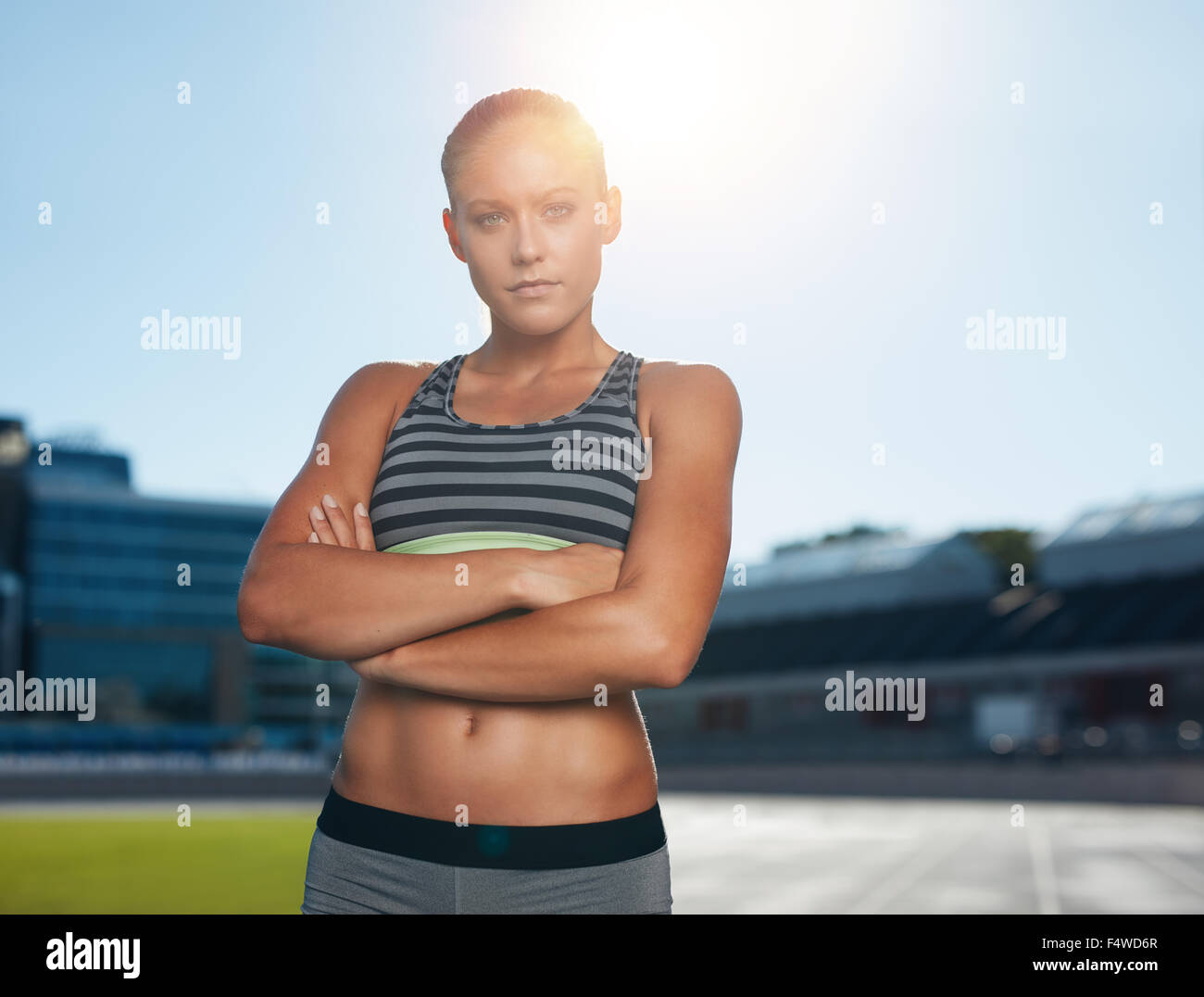 Outdoor shot of professional female athlete standing with her arms crossed and looking at camera confidently. Sprinter - Stock Image
