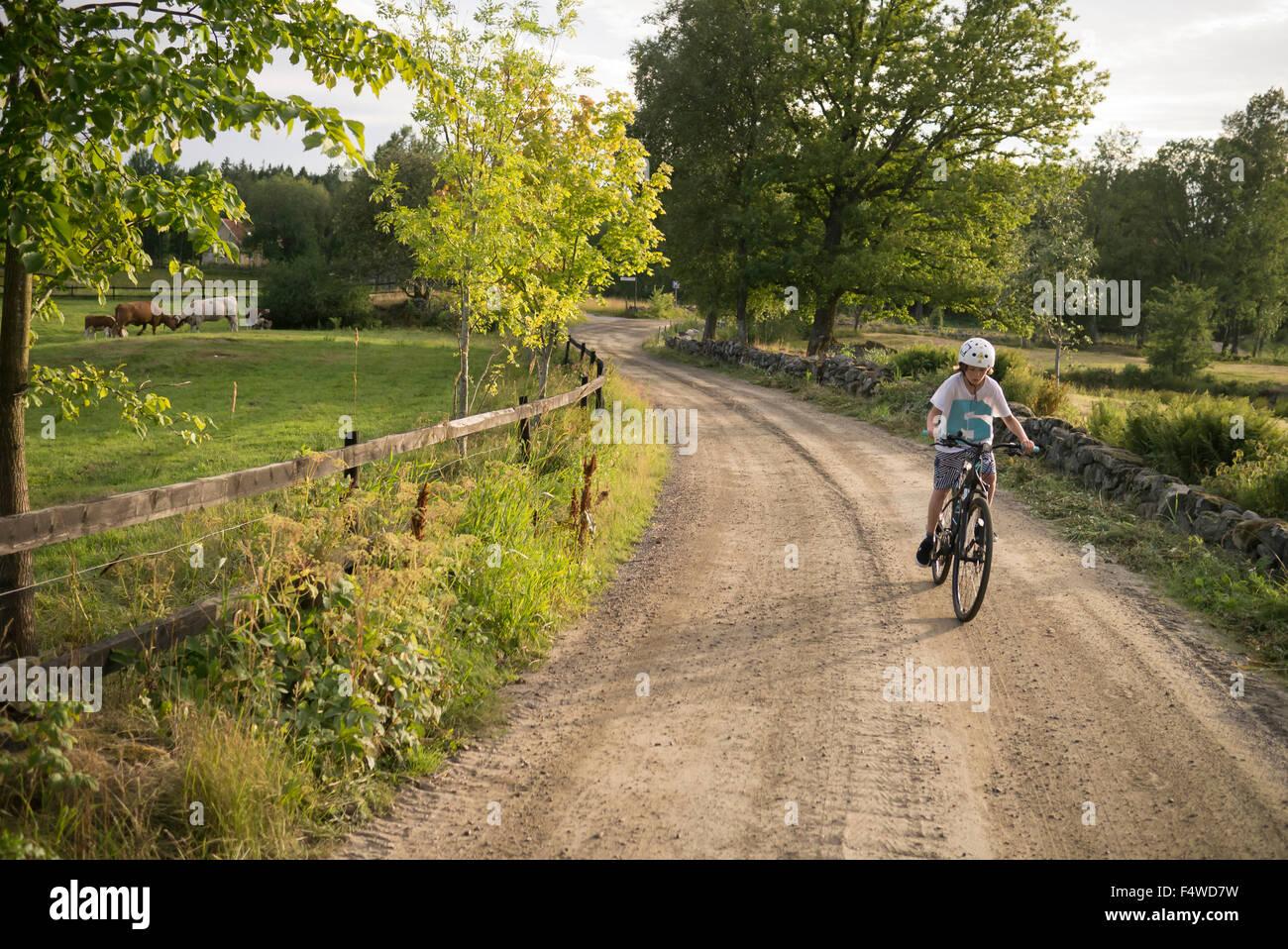 Sweden, Vastergotland, Lerum, Slatthult, Boy (10-11) on bicycle outdoors Stock Photo