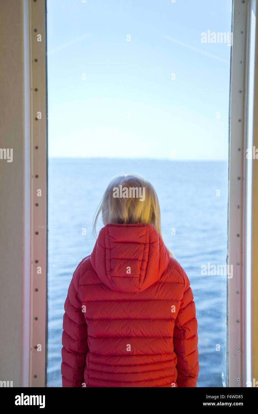 Sweden, Skane, Helsingborg, Girl (8-9) looking through window - Stock Image