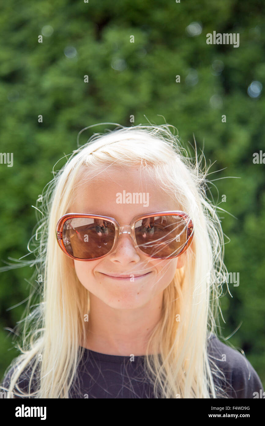 Sweden, Smaland, Anderstorp, Portrait of girl (10-11) wearing large sunglasses - Stock Image