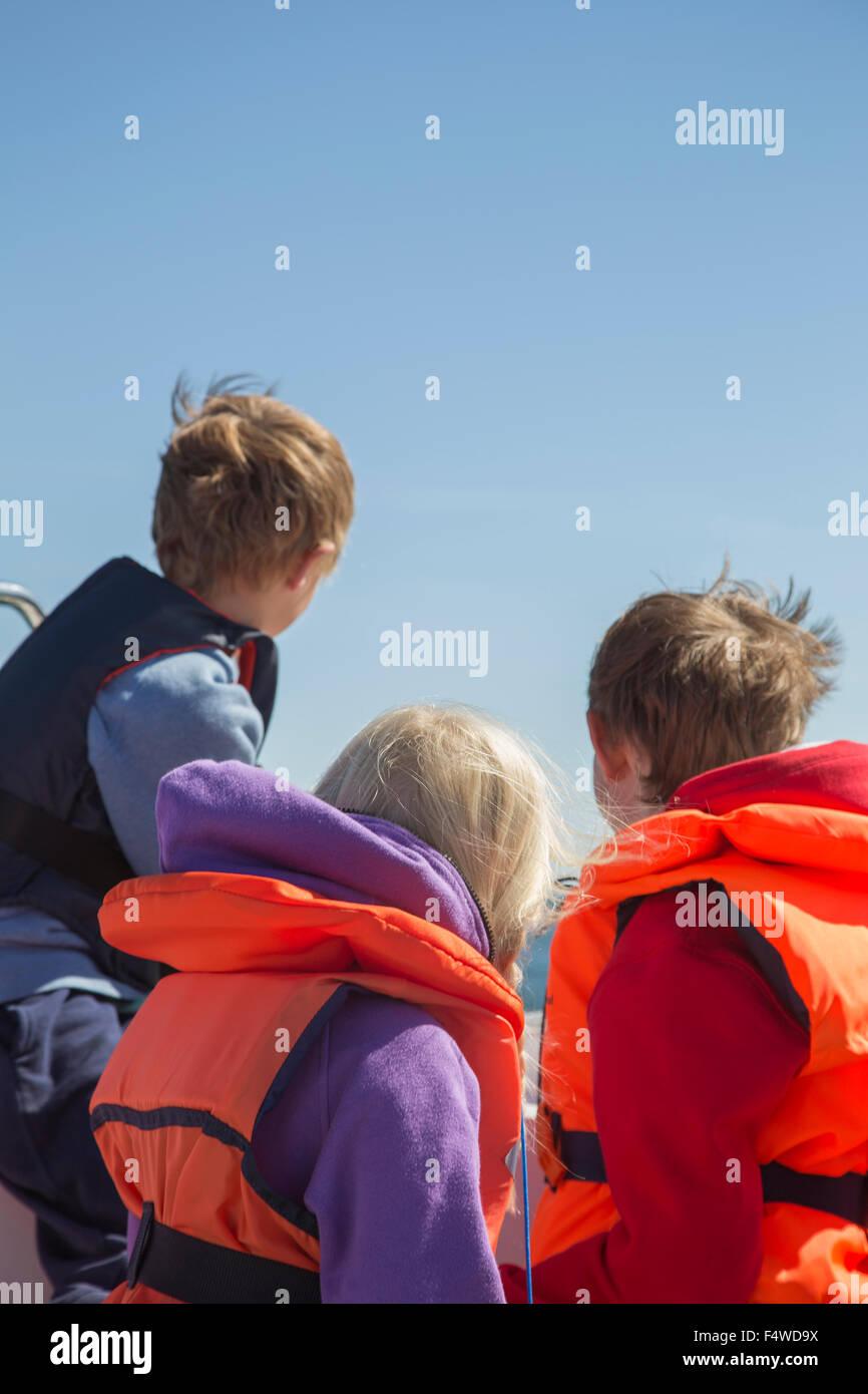 Children (8-9, 10-11, 12-13) on boat Stock Photo