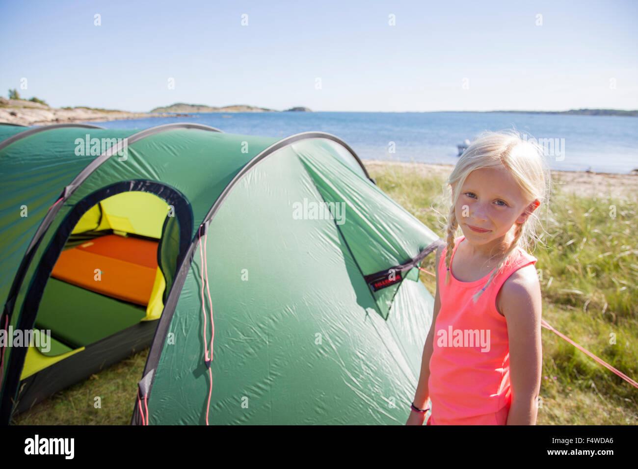 Sweden, Swedish West Coast, Halland, Kungsbackafjorden, Girl (10-11) standing in front of tent - Stock Image
