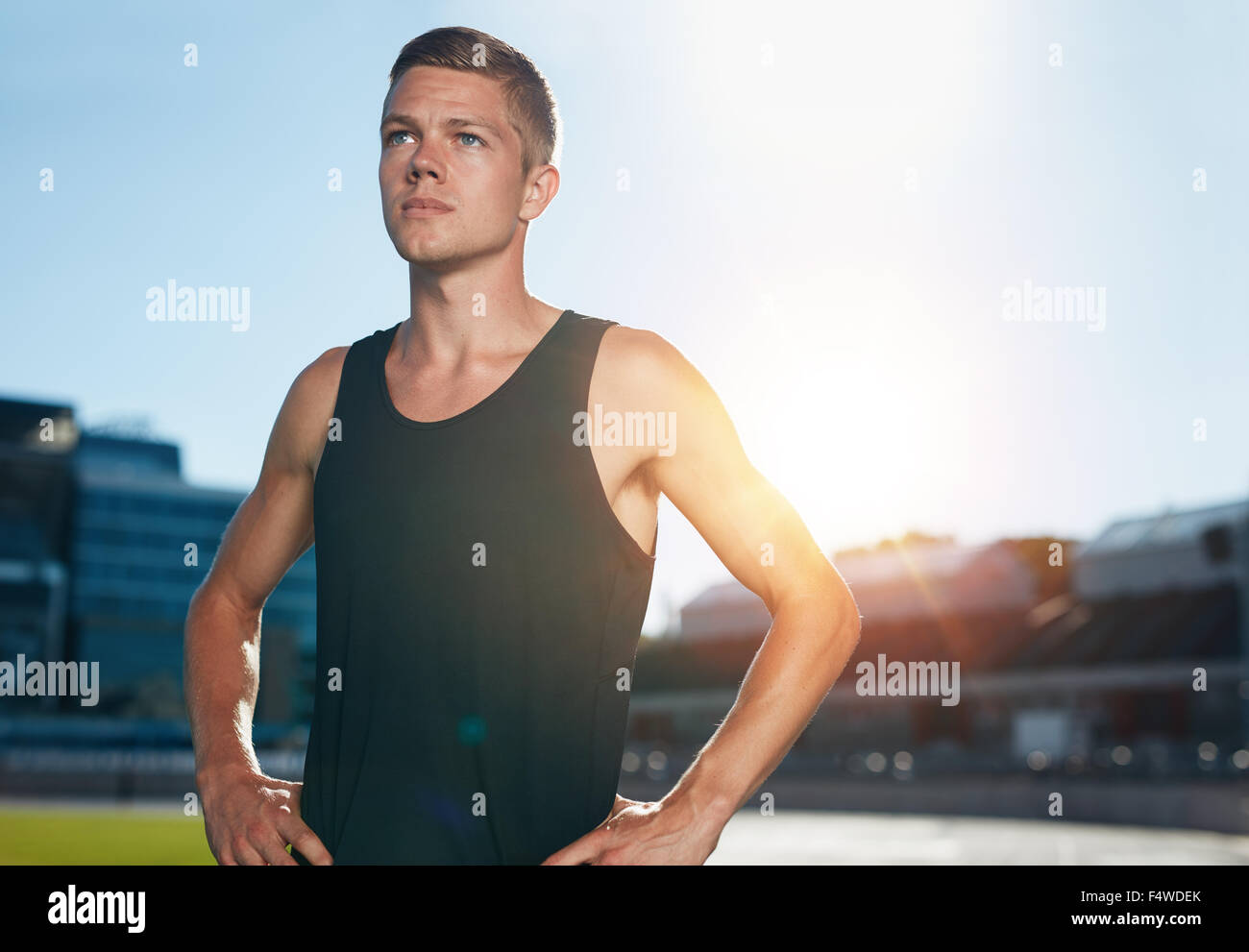 Young male runner standing with his hands on hips looking away. Determined athlete on race track in athletics stadium Stock Photo