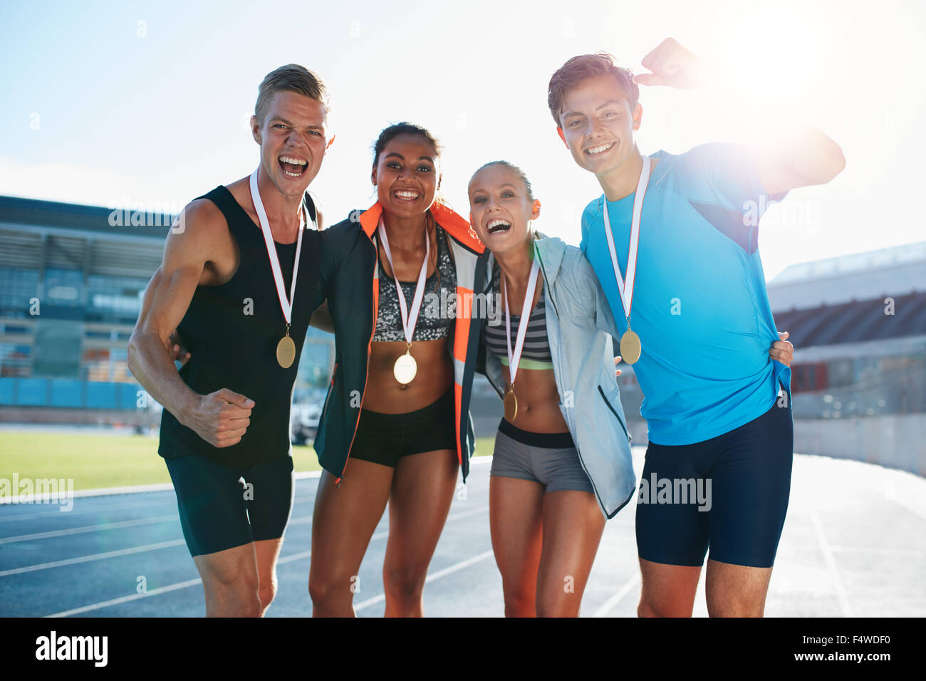 Portrait of young team of athletes enjoying victory. Diverse group of runners with medals celebrating success. - Stock Image