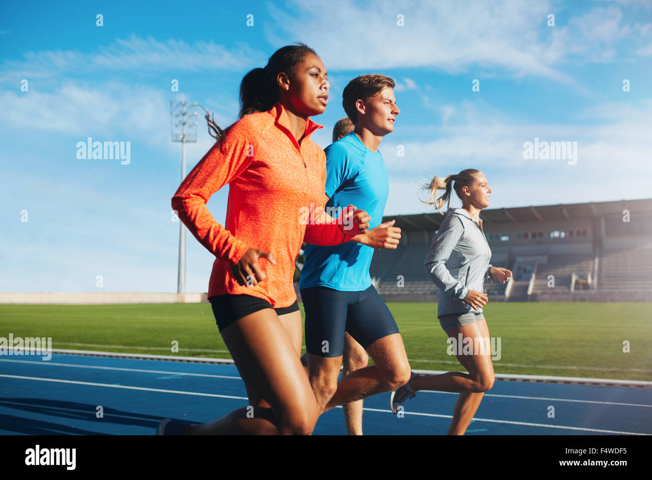 Group of runners running on race track in stadium. Young male and female athletes practicing together on racetrack. - Stock Image