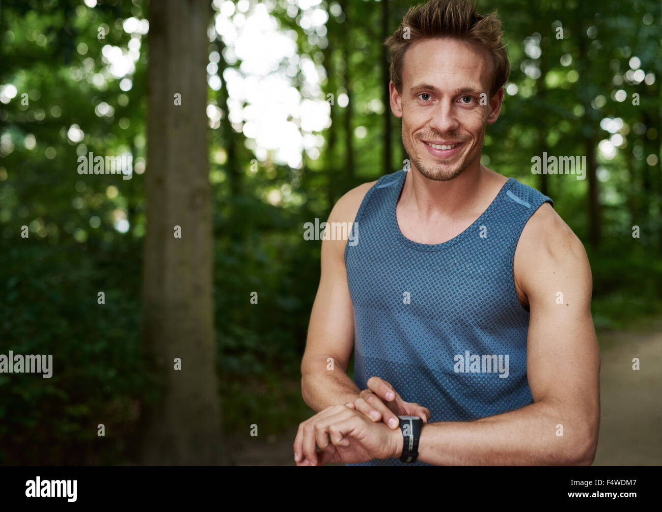 Handsome friendly muscular athlete setting his stopwatch as he prepares for a training run outdoors in the park - Stock Image