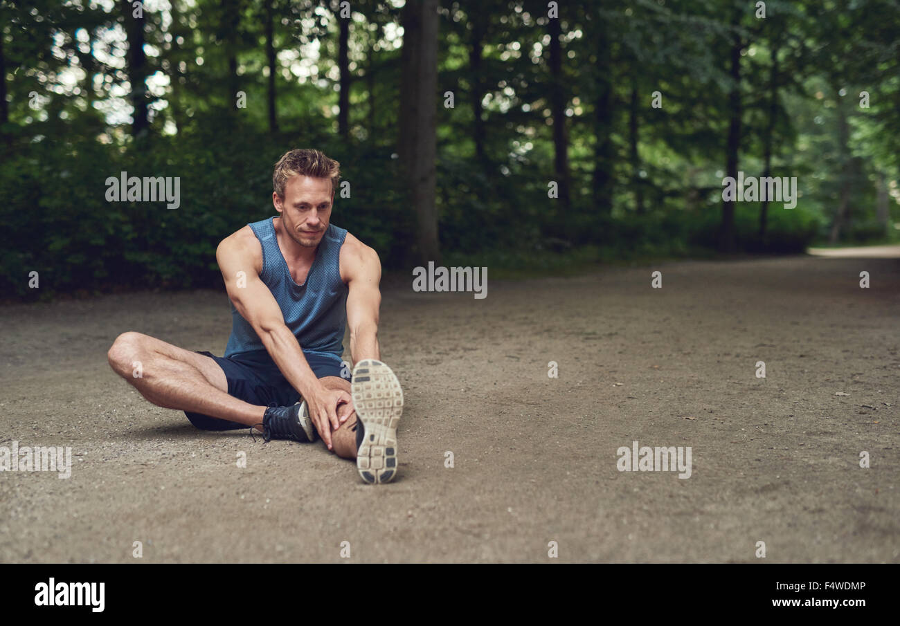 Handsome young male athlete limbering up before training sitting on the ground in a wooded park doing stretching - Stock Image