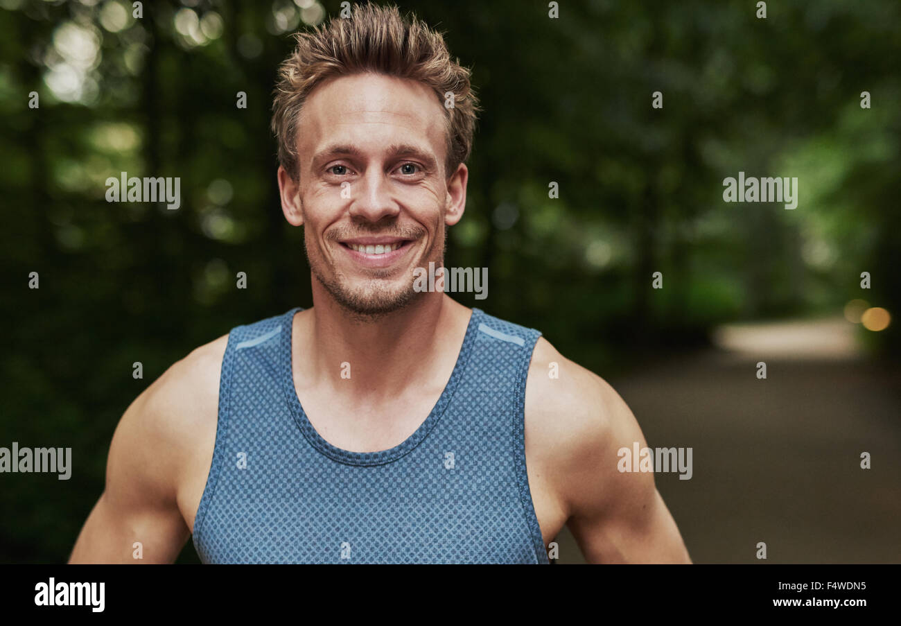 Smiling handsome muscular young man standing outdoors in a wooded park in sportswear looking at the camera, head - Stock Image