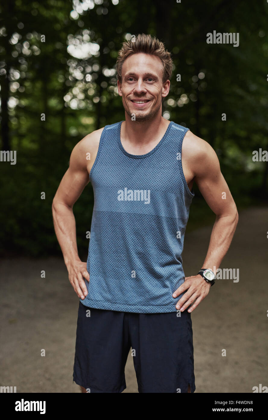 Smiling fit young man enjoying a healthy lifestyle standing outdoors in a park in his sportswear with his hands - Stock Image