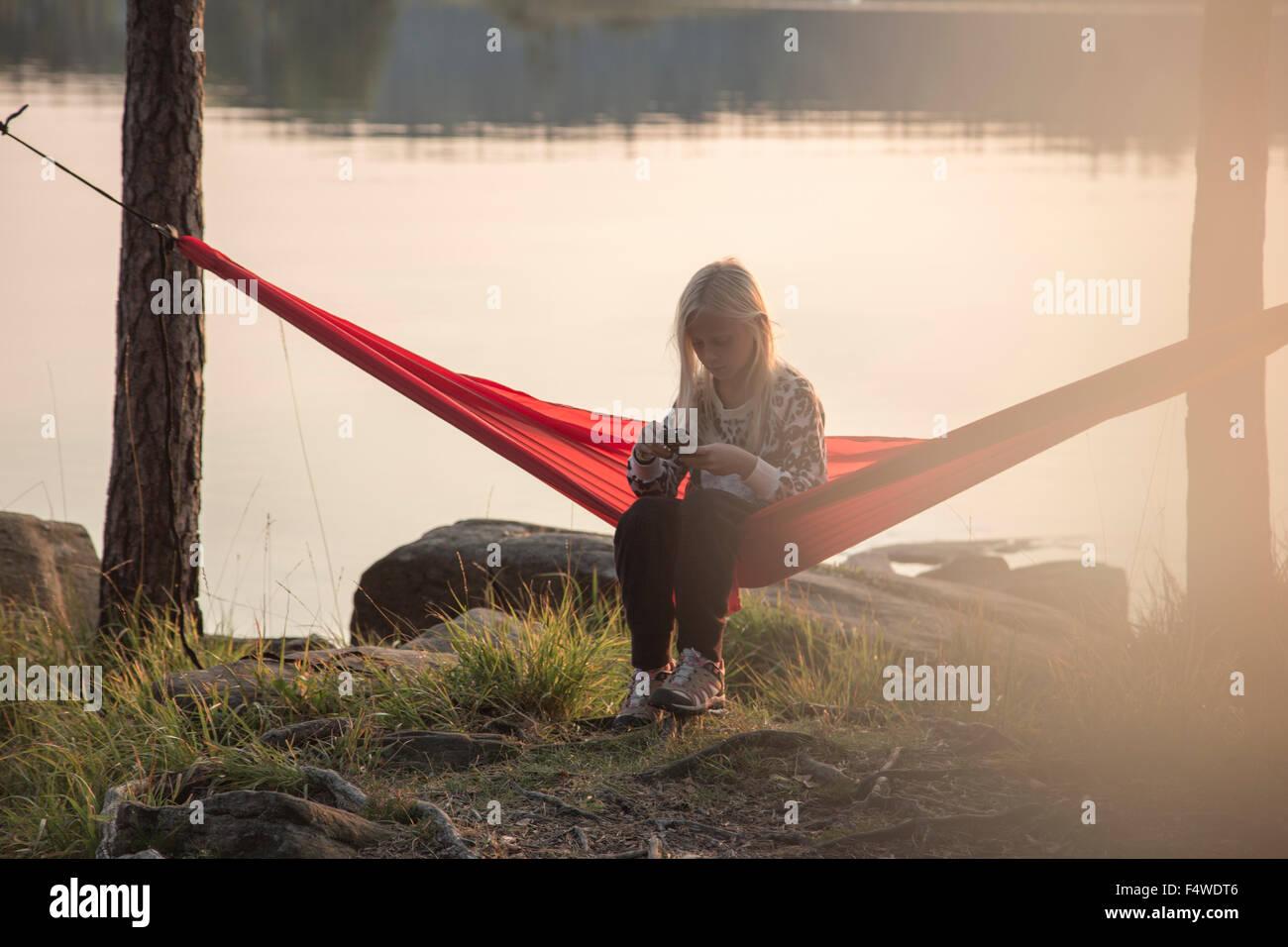 Sweden, Vastergotland, Harskogen, Stora Harsjon, Girl (10-11) relaxing in hammock by lake - Stock Image
