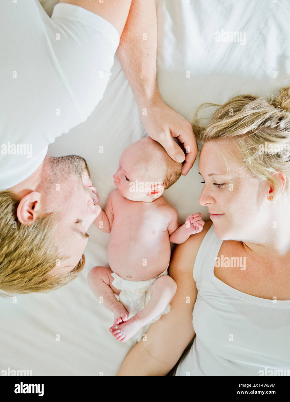 Baby boy (0-1 months) with his parents on bed - Stock Image