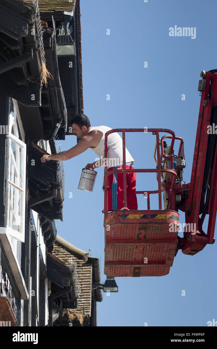 Painter on cherrypicker working on pub frontage. Norfolk Broads England UK Stock Photo