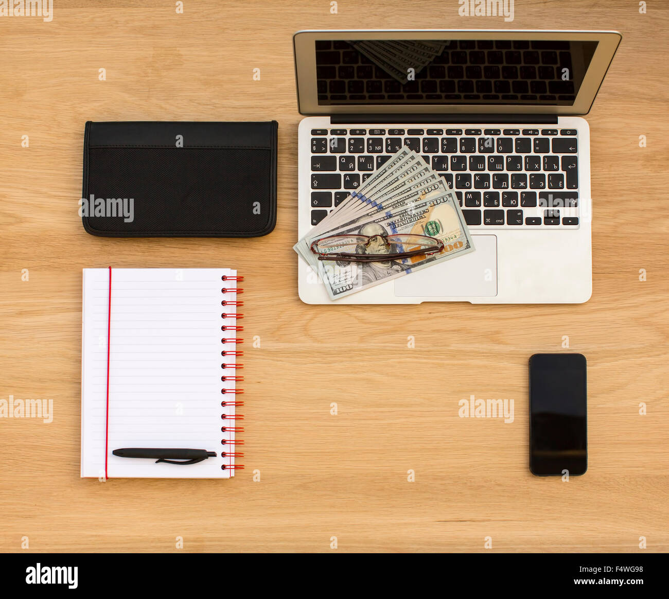 Business concept - laptop, banknotes of us dollars, business card ...