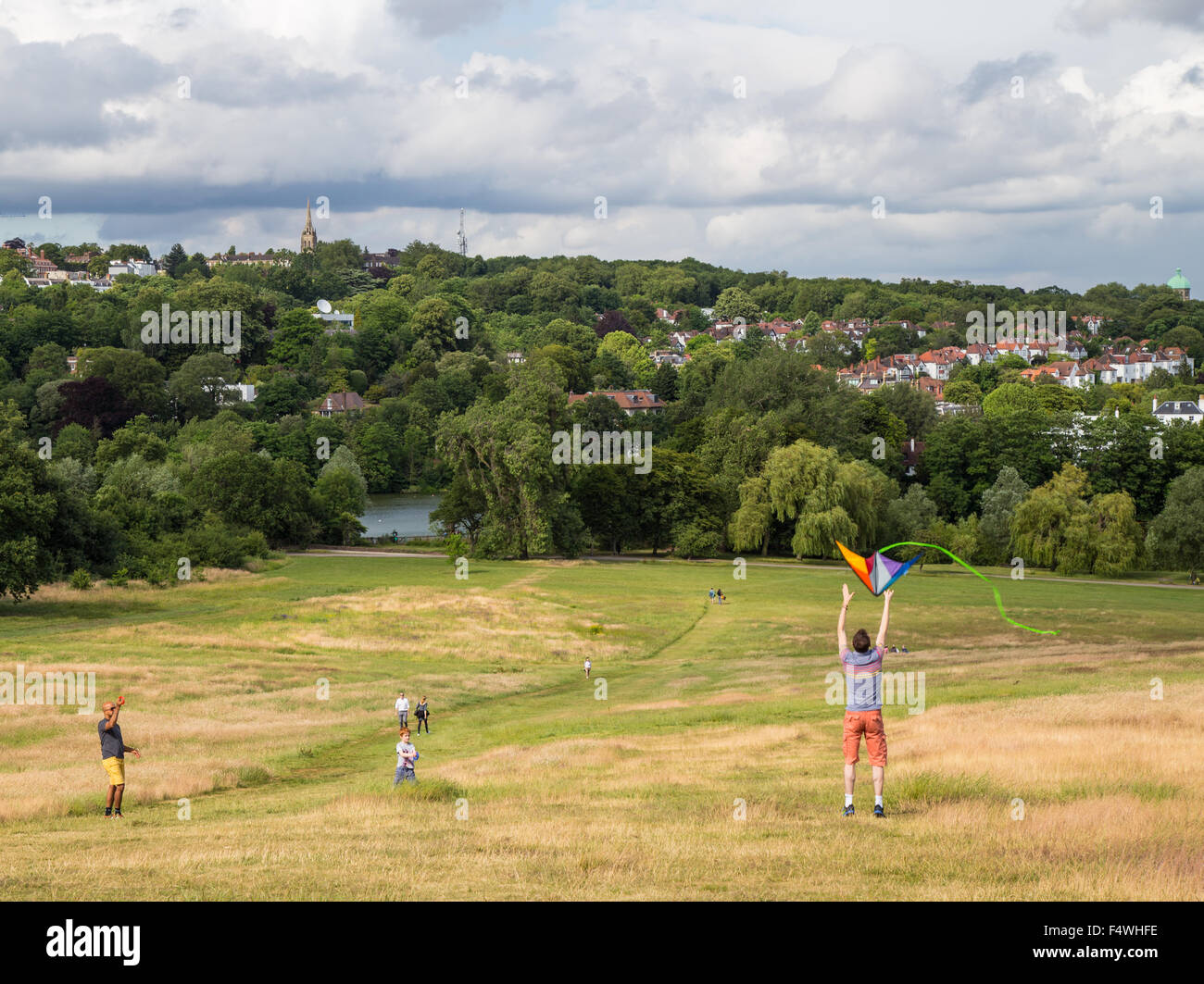 people flying kite on Hampstead Heath, Parliament Hill, London on a summer day - Stock Image