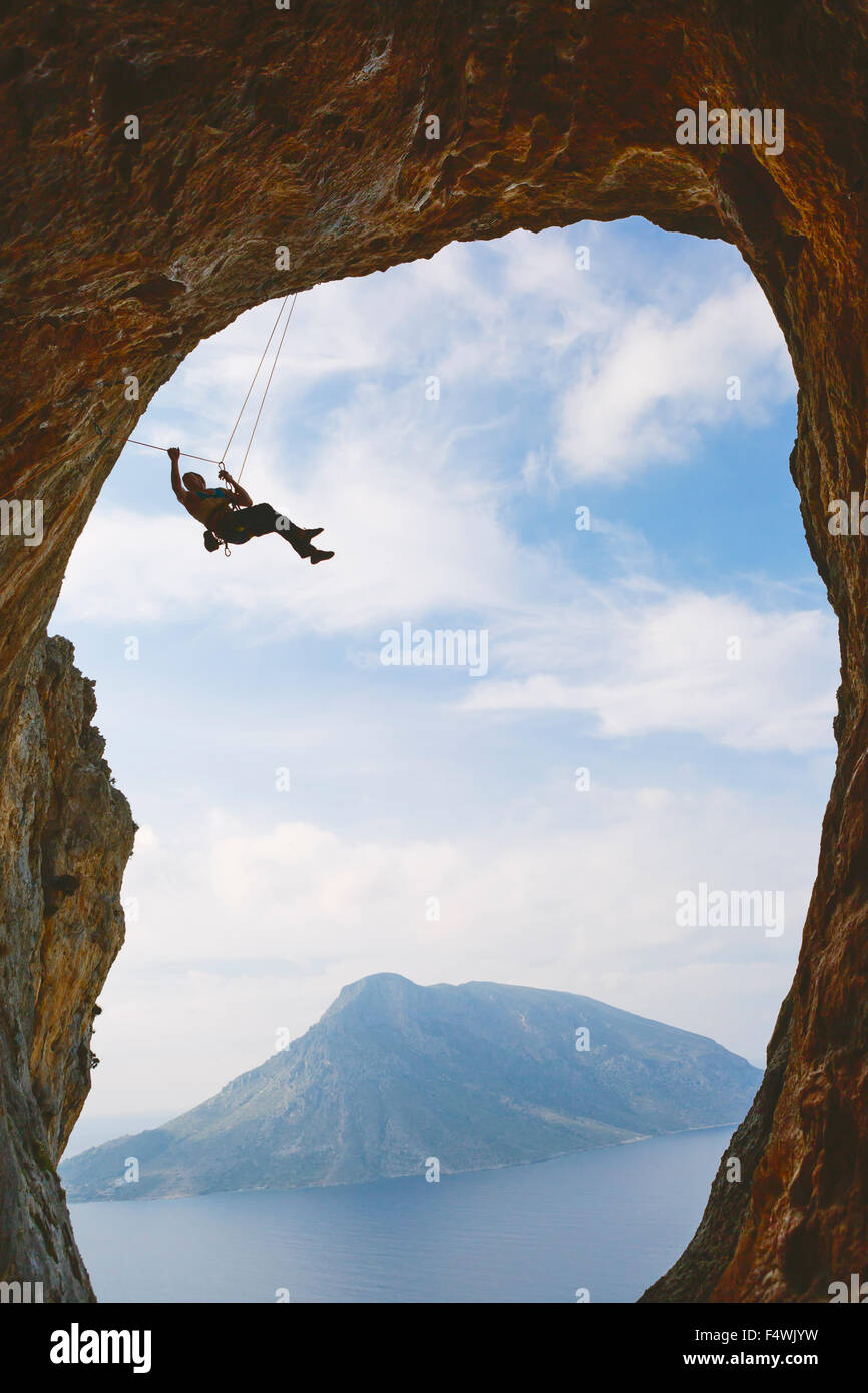 Greece, Dodecanese, Kalymnos, Mountain climbing hanging off natural arch - Stock Image